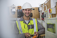 Smiling electrician with hard hat and safety vest - ZEF10904