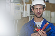 Smiling electrician holding tools - ZEF10919