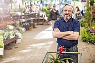Senior man shopping for plants at garden centre - ZEF10970