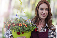 Woman in garden center with potted flowers - ZEF10994