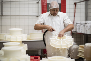 Cheese factory worker cleaning containers with hose - ZEF11018