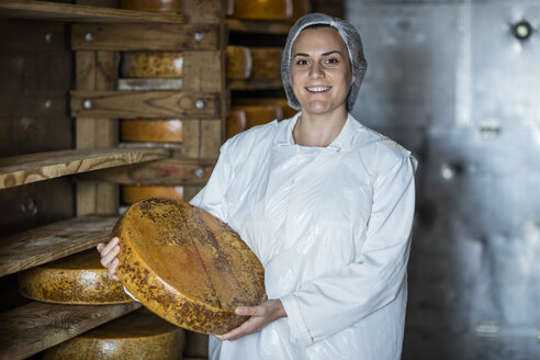 Cheese factory worker proudly holding loaf of cheese - ZEF11027