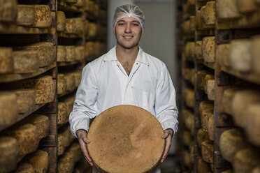 Cheese factory worker proudly holding loaf of cheese - ZEF11060