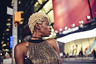 USA, New York City, young woman on Times Square at night watching something - GIOF01572