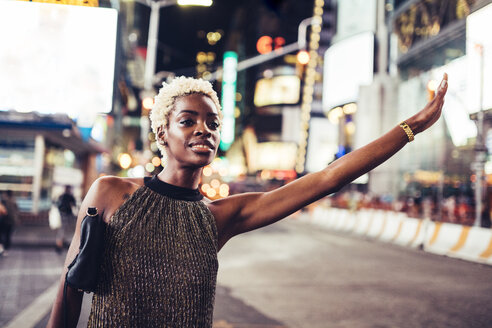 USA, New York City, young woman hailing a taxi on Times Square at night - GIOF01581