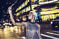 USA, New York City, smiling young woman on Times Square at night taking selfie - GIOF01587