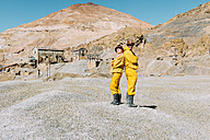 Bolivia, Potosi, two tourists wearing protective clothing standing back to back in front of Cerro Rico - GEMF01169