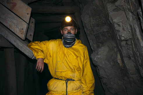 Bolivia, Potosi, tourist wearing protective clothing standing in adit of the Cerro Rico silver mine - GEMF01175