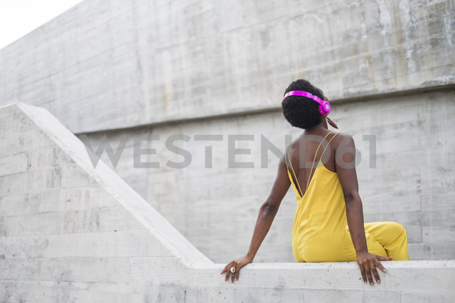 Back view of woman listening music with pink headphones - SIPF00974