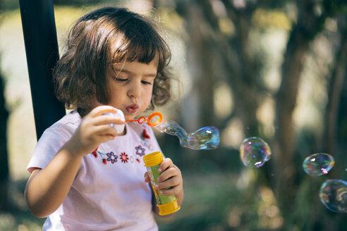 Little girl blowing soap bubbles - LOMF00426