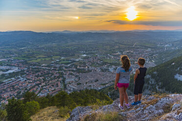 Italy, Gubbio, back view of two children looking at the city from above - LOMF00441