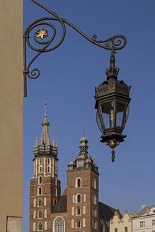 Poland, Krakow, view to St. Mary's Church with historical lantern hanging in the foreground - MELF00153