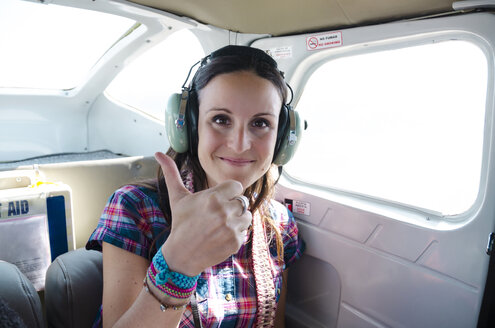 Woman with headphones in light airplane giving thumbs up - GEMF01187