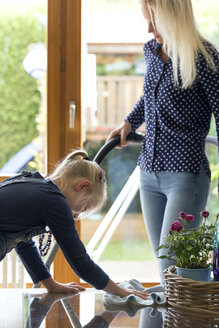 Girl cleaning glass table while her mother hoovering - MIDF00795