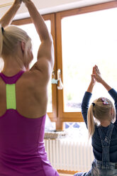 Back view of little girl and her mother practising yoga in the living room - MIDF00798