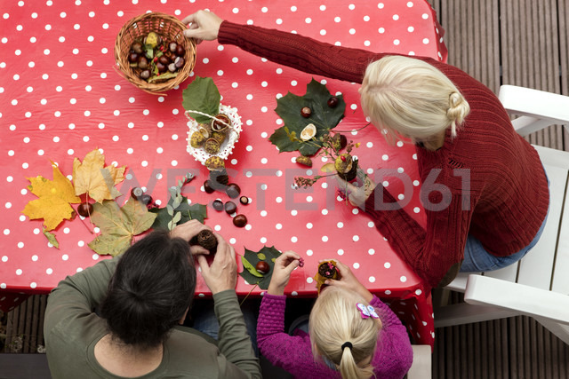 Top view of family tinkering chestnut figurines and autumnal decoration on table at terrace - MIDF00807 - Miriam Dörr/Westend61