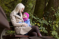 Mother and little daughter sitting on a bench in autumnal forest - MIDF00810