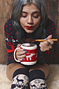 Young woman wearing patterned knit pullover and overknees enjoying hot chocolate in front of wooden wall - RTBF00466