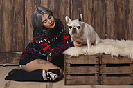 Young woman wearing winter fashion sitting besides her French bulldog - RTBF00469