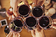 Friends clinking red wine glasses - ZEDF00382
