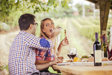 Man feeding woman at outdoor table with red wine and cold snack - ZEDF00385