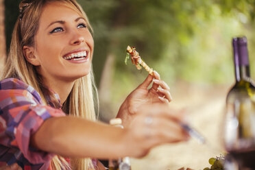 Smiling woman eating outdoors - ZEDF00388
