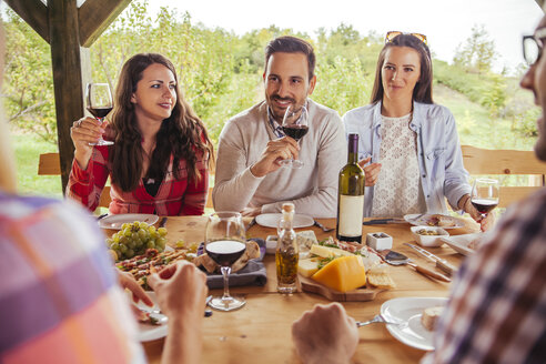 Friends socializing at outdoor table with red wine and cold snack - ZEDF00391