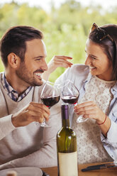 Happy couple clinking red wine glasses outdoors - ZEDF00394