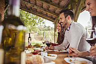 Friends socializing at outdoor table with red wine and cold snack - ZEDF00397