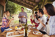 Man giving a speech at outdoor table watched by friends - ZEDF00400