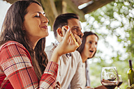 Woman with friends eating outdoors - ZEDF00406