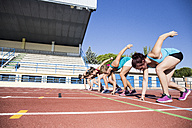 Female runners on tartan track in starting position - ABZF01376