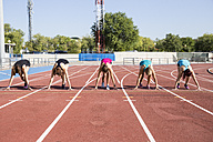 Female runners on tartan track in starting position - ABZF01379
