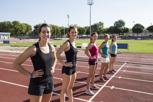 Smiling female runners standing on tartan track at starting line - ABZF01385