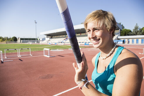 Smiling female pole vaulter preparing - ABZF01391
