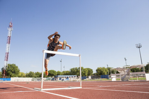 Athlete clearing hurdle during a race - ABZF01403