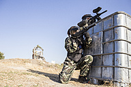 Paintball players aiming with paintball guns during a paintball game - ABZF01421