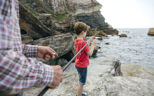 Grandfather and grandson fishing together at the sea - DAPF00413