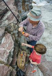 Grandfather teaching grandson fishing at rock coast - DAPF00422