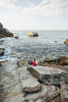 Grandfather and grandson fishing together at the sea sitting on rock - DAPF00428
