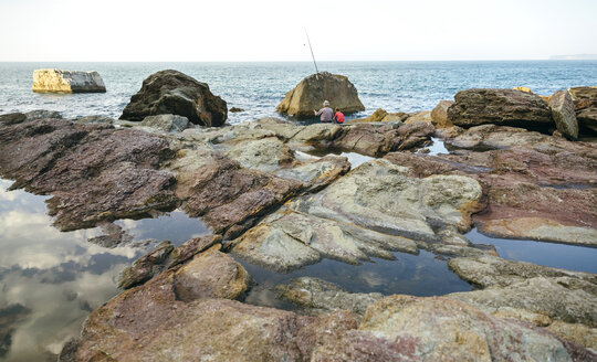 Grandfather and grandson fishing together at the sea sitting on rock - DAPF00431