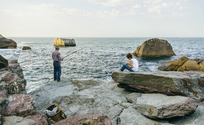 Senior man fishing at the sea with wife sitting on rock - DAPF00434