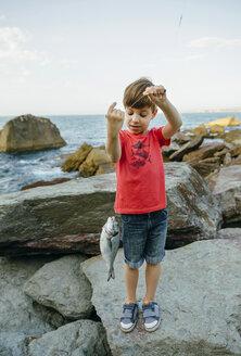 Boy holding fish on fishing line - DAPF00440