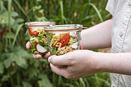 Person holding jars with vegetarian oat salad - EVGF03111