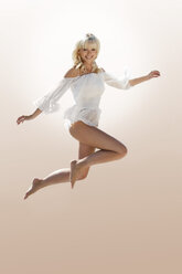 Smiling blond woman jumping in the air - GDF01162