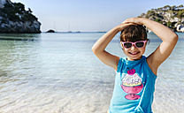 Portrait of smiling little girl wearing sunglasses standing in front of the sea - MGOF02558