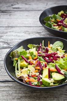 Two bowls of autumnal salad with lettuce, carrots, avocado, beetroot, seeds, pomegranate and quinoa - LVF05496