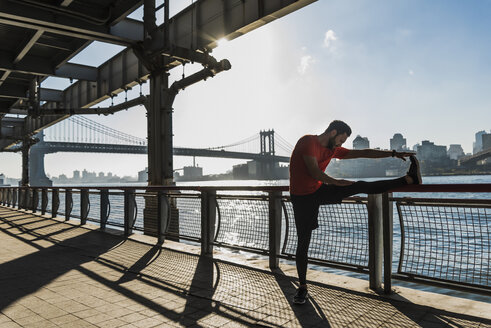 USA, New York City, sportive man stretching at East River - UUF08829