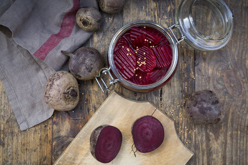 Preserving jar of pickled beetroots and whole and sliced beetroots on wood - LVF05500