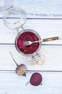 Preserving jar of pickled beetroots and whole and a half beetroot on wood - LVF05506